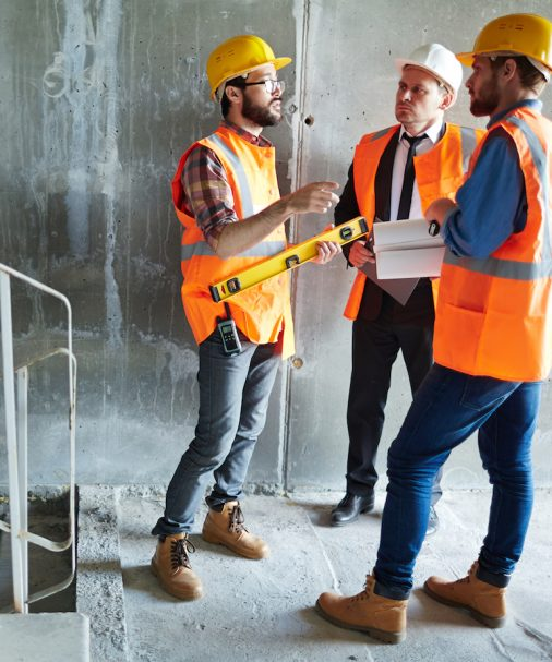 Instructors consulting with each other inside unfinished building